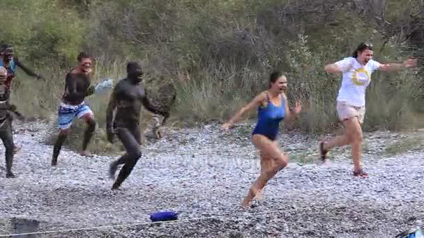 Lidé rozmazaný v bahně honí turisty na oblázkové pláži. Turecko