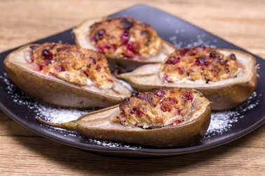 Homemade baked pears with cottage cheese, honey, red cranberries and walnuts in black plate on wooden background, healthy food