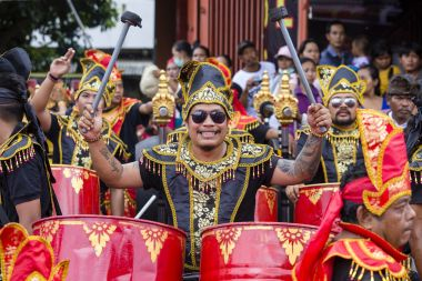 Balinese young guys play on national musical instruments at a street in pre-election rally, the Indonesian Democratic Party of Struggle in Bali, Indonesia