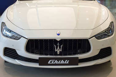 White Maserati Ghibli close up front side view brand logo trident display at showroom dealer at the Siam Paragon Mall in Bangkok, Thailand