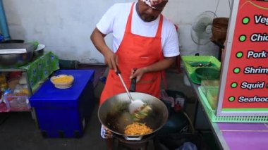 KOH PHANGAN, THAILAND - FEBRUARY 15, 2018 :  Street food : unknown man is cooking pad thai noodle with egg at night food market in island Koh Phangan, Thailand