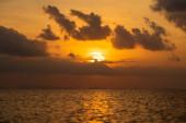 Krásný západ slunce nad mořskou vodou na ostrově Koh Phangan, Thajsko. Cestovní a přírodní koncept. Večerní obloha, mraky, slunce a mořská voda