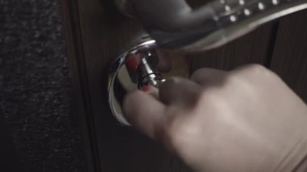 Ženská ruka uzavírá zámek na dveře