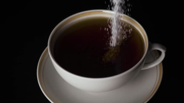Slow mo. Sweetener is poured into a cup of tea