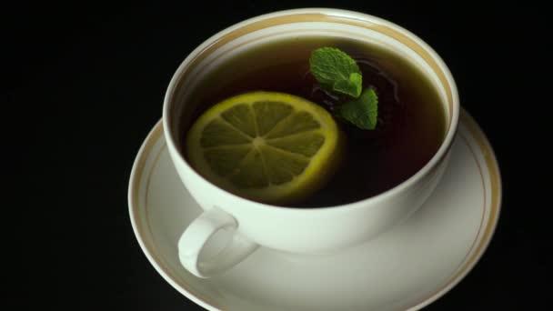 Máta peprná listí padá do čaje. Zpomalený pohyb