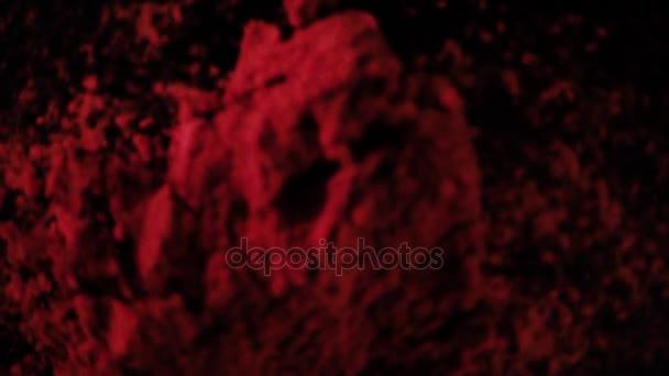 Červený pepř prášek padá dolů. Zpomalený pohyb, pohled shora