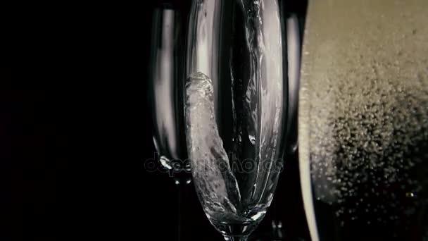 Zpomalený pohyb. Šampaňské se nalije do jedné ze tří brýle