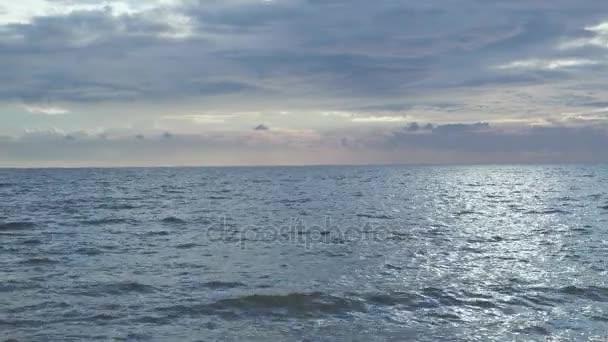 Az elmélkedés, a nap, a tenger felszínén és a köves parton
