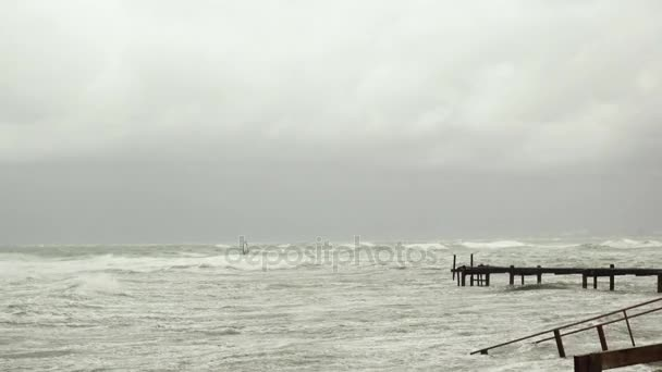 Old pier in the stormy sea and windsurfer