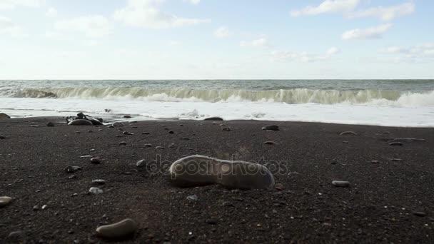 Černé oblázkové, písčité pobřeží a pěny vln Zpomalený pohyb