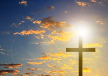 Silhouette cross in blue sky background