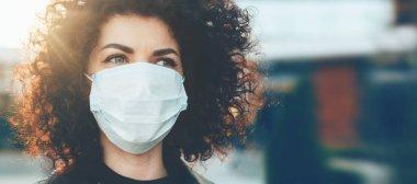 Güzel kıvırcık saçlı beyaz kadın özel maske takarken kendini virüslerden koruyor.