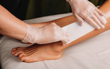 Caucasian spa worker is having a waxing session on legs with his client lying on the couch