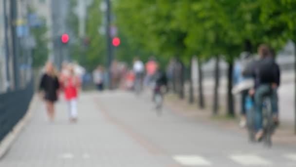 Cyclists move along the bike path, pedestrians walk along the sidewalk