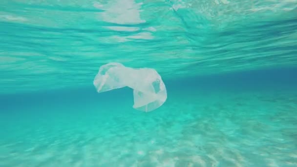 Camera Is Swimming Around A Plastic Bag Floating Underwater. Tropical, Sunny, Summer, Landscape With A Sun Flooded Sandy Seabed.