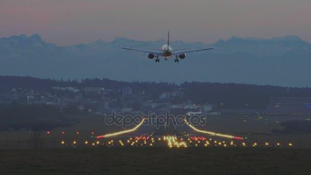 Letadlo přistává na letiště v Curychu za soumraku s Alpami v pozadí