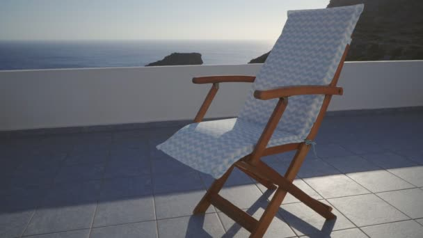 Empty Deck Chair On A Breezy Terrace By The Blue Sea In Summer Holiday  Resort In Greece