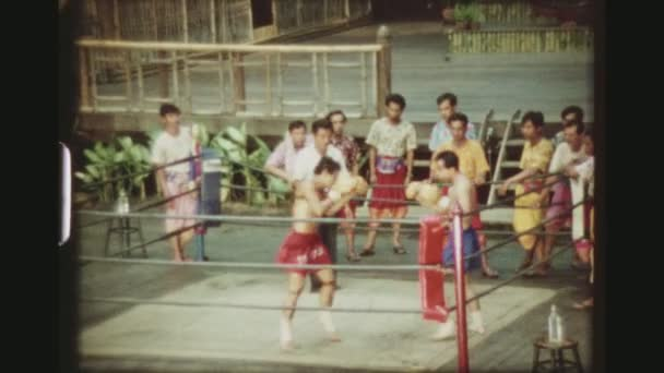THAILAND, BANGKOK SAMPRAN RIVERSIDE, MAY 1978. Two Shot Sequence Of Male Muay Thai Boxers Hitting Each Other Hard, Until One Hangs In the Ropes And The Referee Has To Pause The Match, At The Cultural Village Show.