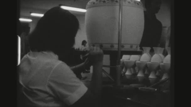 Tchaj-wan, Taipei, duben 1978. Dva výstřel sekvence s dvou zaměstnankyň pečlivě Malování květinové vzory na vázy v keramické dílně v okrese Yingge s turistů