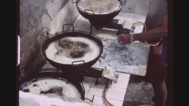 Španělsko, Mallorca, červenec 1983. Tři výstřel sekvence nativní muže vařit fritovací čerstvé sardinky v obrovské hrnce nad plynové plameny venku, při kouření cigaret