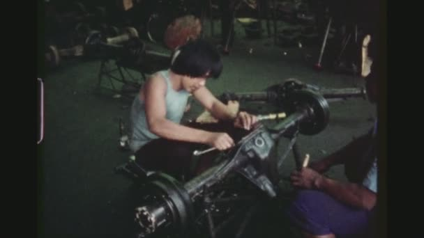 PHILIPPINES, CITY OF LAS PINAS, APRIL 1978. Two Shot Sequence Of Male Employees Assembling Parts Of A Wheel Axle Of Jeepneys Inside The Sarao Motors Manufacturing Plant.