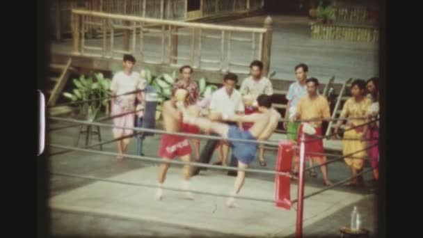 THAILAND, BANGKOK SAMPRAN RIVERSIDE, MAY 1978. Two Male Muay Thai Kickboxers Deploying Leg Kicks At Each Other At The Cultural Village Show, At The Sampran Riverside.