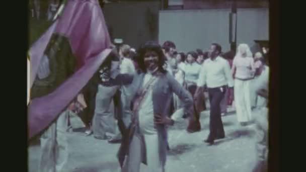 Brazílie, Rio De Janeiro, v březnu 1976. Žena s vlajkou a muž tančit Samba A přeplněné veřejné průchodné strany prohybu, staří i mladí lidé užívají