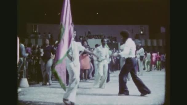 Brazília, Rio De Janeiro, március 1976. Fiatal brazil pár gazdaság egy nagy zászló és Spinning együtt a Samba táncparketten, tudásukat a nyilvános Open Air Club