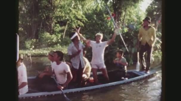 thailand, bangkok, 1978. zwei schusssequenzen einer mannschaft junger männer jubeln freudig nach einem bootrennen auf einem langboot, halten hoch und winken mit den paddeln.