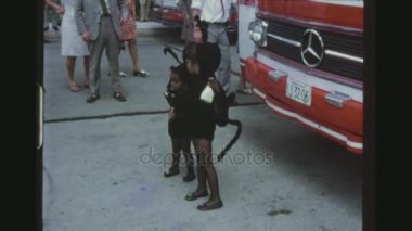 VENEZUELA, MANAGUA, MAY 1971. Two Shot Sequence Of Two Little Girls In Black Ant Outfits Posing Infront Of A Tourist Bus.