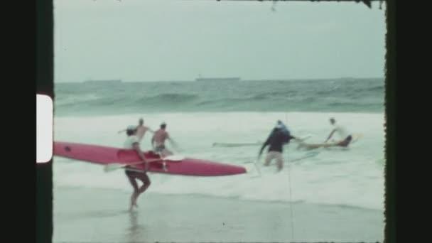 Austrálie, Perth, březen 1971. Dva výstřel sekvence konkurenčních plavčíků, běh s jejich surfovací prkna do moře během australského surfovat záchranné mistrovství