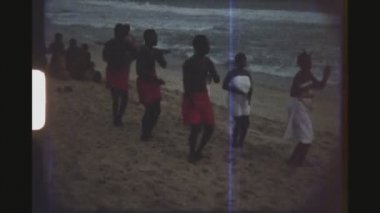 GHANA, BUSUA, APRIL 1976. Group Of Male And Female Dancers In Traditional Outfits Dancing On The Beach At Dusk With A Band In The Background.