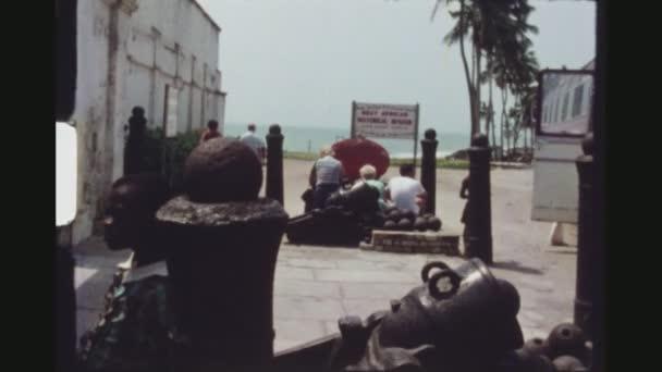 Ghana, Elmina, duben 1976. Turisté u vchodu západní Afriky historické muzeum mezi kanóny a dělové koule. Africké dítě v popředí při pohledu na fotoaparát