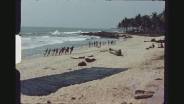 Ghana, Busua, duben 1976. Skupina rybářů, vytáhl své rybářské sítě na pláži, zatímco turisté filmové akce