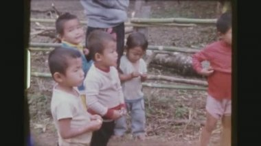 THAILAND, MAE SALONG, DECEMBER 1983. Two Shot Sequence Of Colorful Karen Hill Tribe Children With Grandmother Smoking A Pipe.