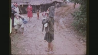 THAILAND, CHIANG RAI PROVINCE, DECEMBER 1983. Two Shot Sequence With Zoom Of An Akha Hill Tribe Woman Begging For Money, Getting Photographed By Tourists And Surronded By Children.