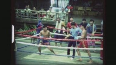 THAILAND, BANGKOK SAMPRAN RIVERSIDE, DECEMBER 1983. Two Male Muay Thai Kickboxers Battling Each Other In A Hard Knee Kicking Match At The Cultural Village Show.