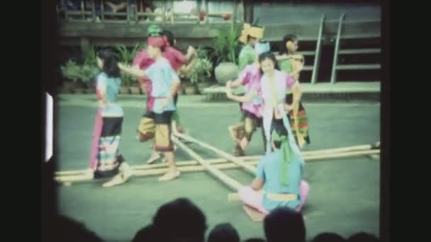 THAILAND, BANGKOK SAMPRAN RIVERSIDE, DECEMBER 1983. Four Couples In Colorful Costumes Demonstrate The Bamboo Dance, The Lao Kratop Mai, Perfectly Synchronized At The Cultural Village Show.