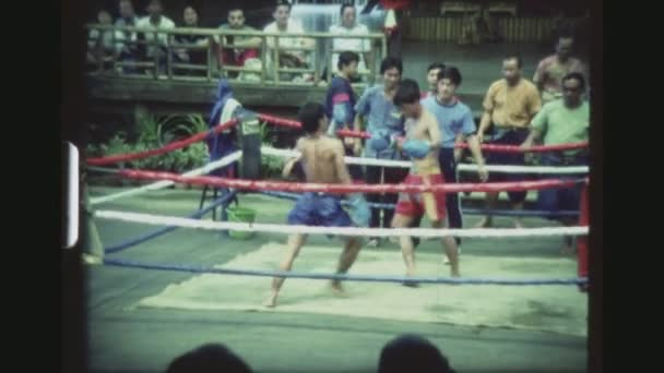THAILAND, BANGKOK SAMPRAN RIVERSIDE, DECEMBER 1983. Two Muay Thai Kickboxers Hitting Each Other With Kicks, Punches And Leg Sweeps, Until One Falls Down At The Cultural Village Show.