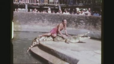 THAILAND, BANGKOK, JANUARY 1984. Two Shot Sequence Of A Crocodile Handler Laying On Top Of A Big Alligator At The Samutprakarn Crocodile Farm Show.
