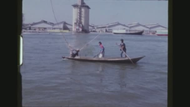 Thajsko, Bangkok, prosinec 1983. Tři rybáři na dlouhé tradiční dřevěné rybářské lodi s aktivována otevřenou síť, veslovat zpět do Bangkoku Harbor