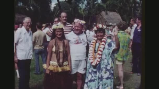 usa, hawaii, honolulu april 1977. porträt eines erwachsenen männlichen touristen mit zwei weiblichen hula-tänzerinnen in seinen armen, bei der kodak hula show.