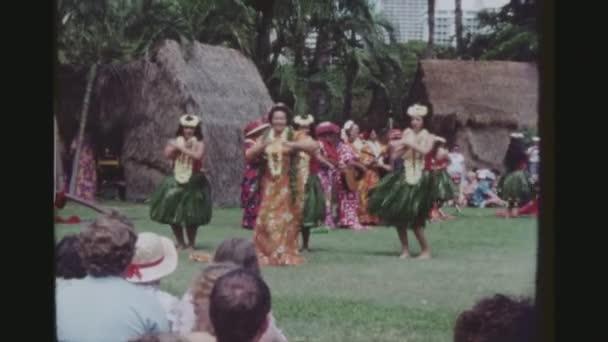 usa, hawaii, honolulu april 1977. zwei schusssequenzen. alte und junge Hula-Tänzerinnen treten gemeinsam bei einem traditionellen Luau bei der Kodak Hula Show auf.