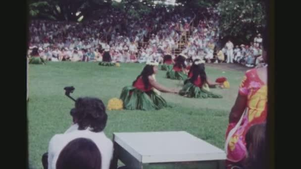 usa, hawaii, honolulu april 1977. gruppe von hula-tänzern, die mit kala au sticks auf dem rasen bei der kodak hula show vor einem großen touristischen publikum auftreten.