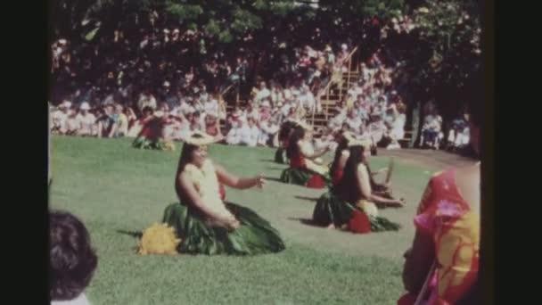 usa, hawaii, honolulu april 1977. gruppe von hula-tänzern, die mit pu ili bambusrasselstöcken bei der kodak hula show vor einem großen touristischen publikum auftreten.
