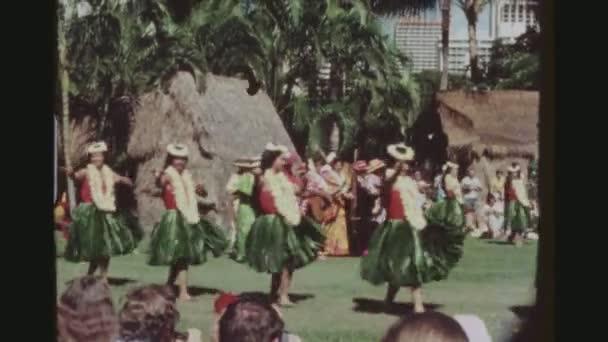 usa, hawaii, honolulu april 1977. zwei schusssequenzen von hula-tänzerinnen in traditionellen ti-blatt-röcken, tanzen und eine reine weibliche band, die musik bei der kodak hula show spielt.