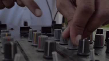 Slow Motion Close Up Of Male Dj Hands Mixing A Track  On An Audio Console During A Summer Party Outdoors