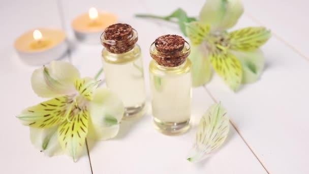 Az aromaterápia, spa koncepciója. Üvegek virágos illóolajjal fehér fa háttéren. A közelben van egy sárga virág. A szirmok fentről hullanak..