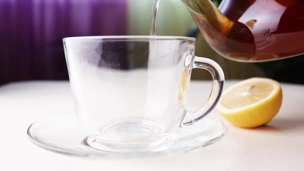 Horký bylinkový čaj z konvice se nalije do průhledného šálku. Nedaleko leží citron. Koncept zdravých organických nápojů.