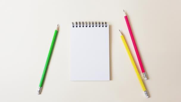 Irodai tárgyak fokozatosan jelennek meg egy könnyű háttér: notebook, ceruzák, gemkapcsok, tollak, gemkapcsok, gombok. A tanulás, az iskola, az üzlet, a kreativitás, a hobbi fogalma. 4k mozgás leállítása.